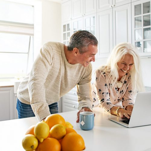 Senior couple relaxing together in the kitchen with a laptop computer surfing the internet with a healthy bowl of citrus fruit in the foreground